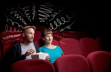 Cute couple in cinema watching movie