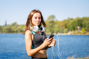 Young sporty woman with smartphone on training . Smiling girl with headphones on outdoor workout at summer morning