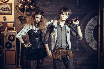 Young beautiful couple in suits in steampunk style wearing glasses and with guns.