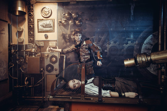 A scientist, a mechanic, includes a control lever to revive an artificial robot girl on a desk in his steampunk lab.