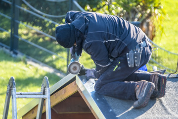 Roofer repairing the metal facing after storm