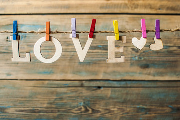 words Love hang with rope on wood background (Valentines day)