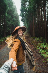 Woman holding hand of photographer in woods