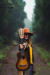 Woman showing ukelele in woods