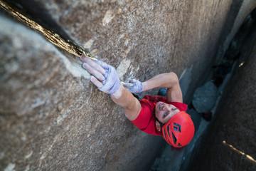 Shirtless man rock climbing a thin splitting crack in Joshua Tree