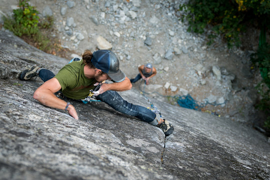 Male climber placing cam protection on a thin finger crack trad climb in Yosemite