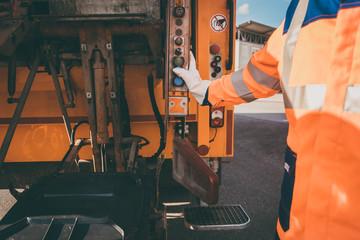 Arbeiter bei der Müllentsorgung leert Mülltonne in Entsorgungsfahrzeug zur Entsorgung