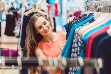 Frau sucht nach Kleid auf Kleiderstange im Mode Laden und sieht glücklich aus