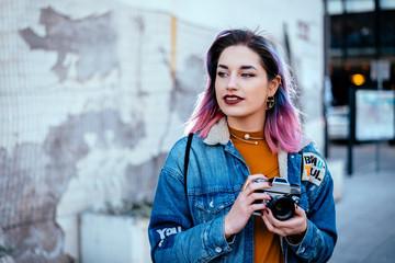 Beautiful urban girl photographer looking away, holding a camera.