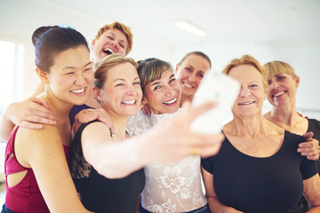Laughing group of friends taking selfies in a dance class