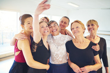Smiling group of friends taking selfies in a dance studio