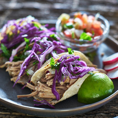 colorful plate of three mexican carnitas street tacos with cilantro and red cabbage