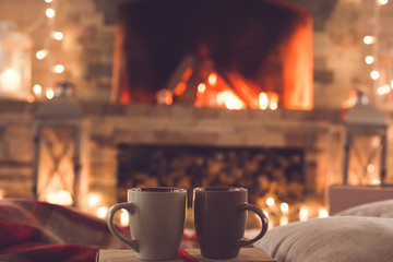 Two cups near the fireplace winter romantic concept