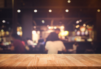 Wood table top (Bar) with blur people siting night cafe,restaurant background .Lifestyle and celebration concepts