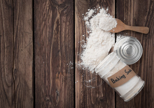 Jar of baking soda with text space on wood background,top view