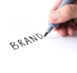 """Hand holding black permanent marker and writing word """"BRAND""""on white background"""