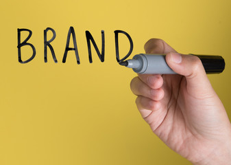 """Hand holding black permanent marker and writing word """"BRAND""""against yellow background"""