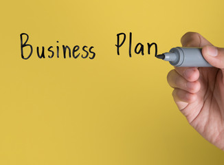 """Hand holding black permanent marker and writing word """"Business Plan""""against yellow background"""