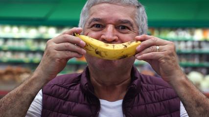 Senior Man Smiling With Banana