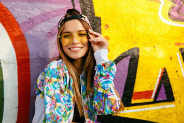 Beautiful smiling girl in eyeglasses, posing at camera. Dressed in stylish jacket and cap. Outdoors, graffiti wall