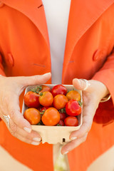Woman shopping for fresh vegetables produce at a farmers market. Close up of hands holding a pint basket container with bright, fresh, ripe, organic red and orange cherry tomatoes.