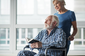 Tranquil senior husband sitting in wheelchair and holding the Bible. His calm wife standing near him. Concept of care. Copy space in left side