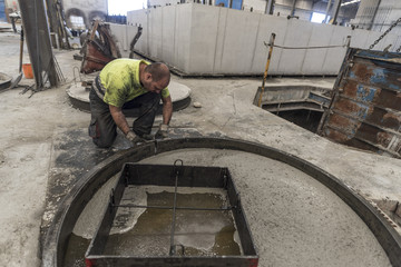 Man working with concrete mold in construction structures factory