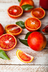 Bloody red oranges slices with leaves on wooden background