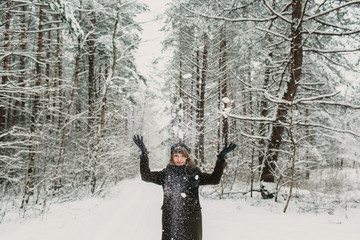 Cheerful woman having fun in winter forest