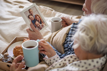 Old man holding frame with photo. Senior married couple looking at photograph and holding cups of tea