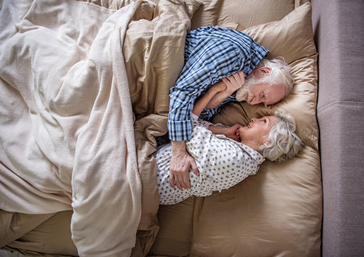 I love you. Top view of glad senior husband and wife sleeping in bedroom. They are hugging and looking at each other with smile