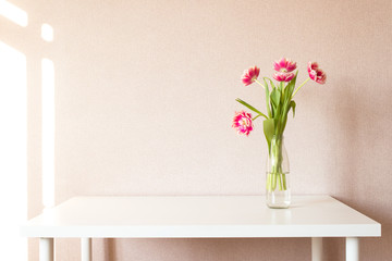 Bouquet of tulips on white table. Work space. Sunny day.