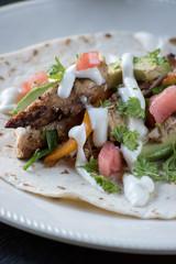 chicken fajitas with guacamole, tomatoes, peppers, cilantro, and sour cream on tortilla shell