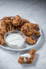 chicken wings with ranch dressing on white plate in bright setting