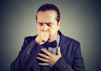 Man coughing heavily on gray