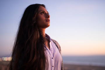 Young Indian woman looking up sunset sky