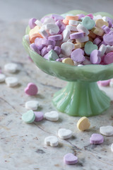 candy hearts in pastel colors in green glass bowl