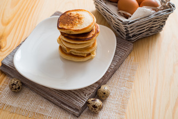 Stack of pancakes in white saucer on light wooden table