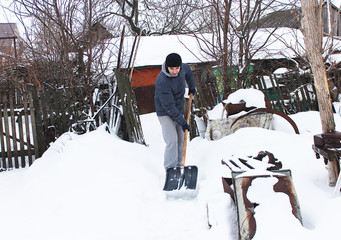 A young man cleans the snow, a big shovel in a rural yard