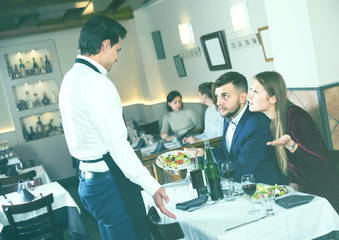 angry guests conflicting with waiter in restaurant