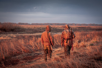 Hunters hunting in rural field during sunrise. Field painted with orange color of rising sun