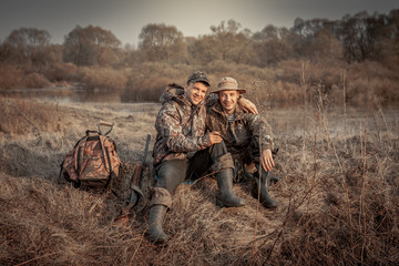 Fotobehang Jacht Hunter men friends resting in rural field during hunting period symbolizing strong friendship