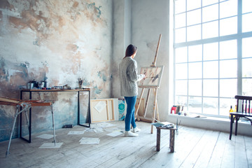 Young woman artist painting at home creative standing drawing