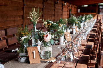 Table decor with white flowers and candles for a wedding party.