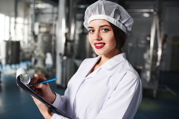 a pretty young girl scientist or worker in white uniform makes notes on paper against the background of modern factory equipment.