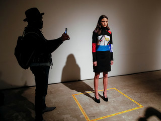 A visitor takes pictures as a model presents a creation by Ukrainian designer Ksenia Schnaider during Ukrainian Fashion Week in Kiev