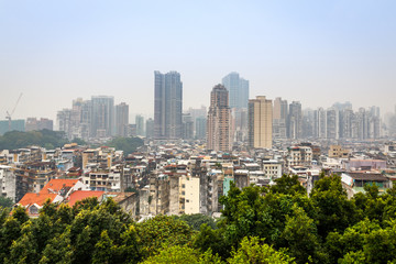 Macau city center panorama with slums and tall living buildings with trees in foreground, China