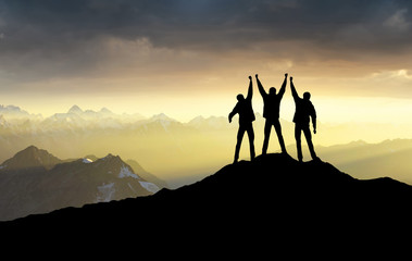 Silhouettes of team on mountain peak. Sport and active life concept.