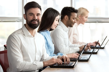 Cheerful smiling bearded caucasian man in office. Young adult bearded man smiling sitting in bright office woth colleagues.