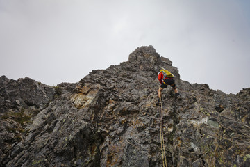 Low angle view of determined hiker climbing mountain against sky